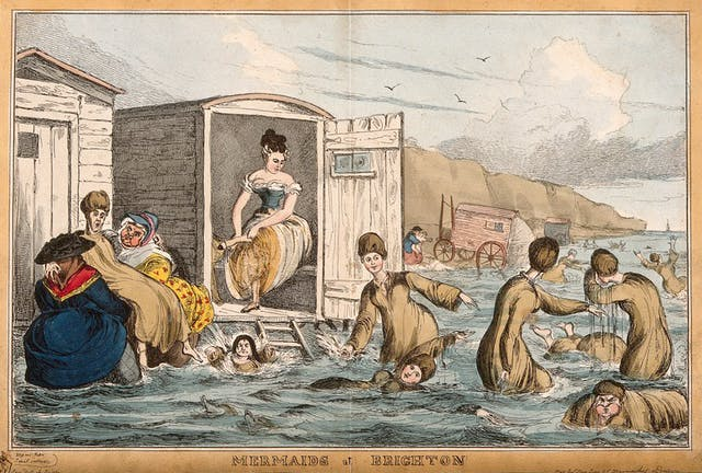 Women bathing in the sea, one changing into swimming clothes in a wooden bathing machine, another is helped into the water by two large fully dressed women.