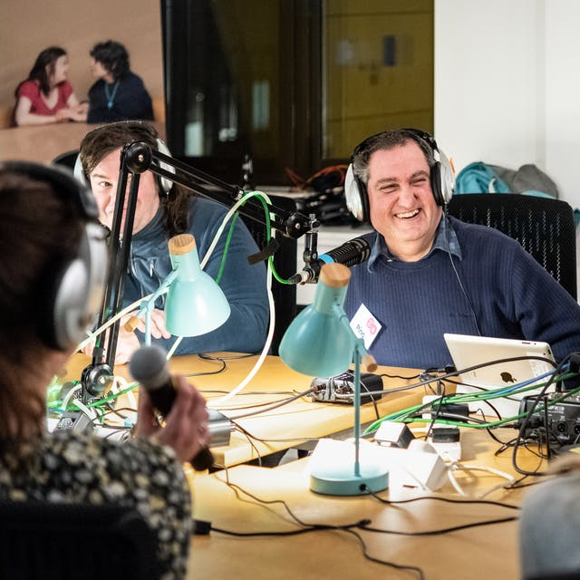 Photograph of a group of people sat around a table hosting a radio show. They are wearing headphones. The table is covered in wires from desk lamps, microphones and tablet devices. In the centre of the image one of the people is laughing.