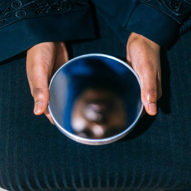 Photograph of a woman holding a circular mirror on her lap with both hands. In the reflection you can see her face, out of focus.