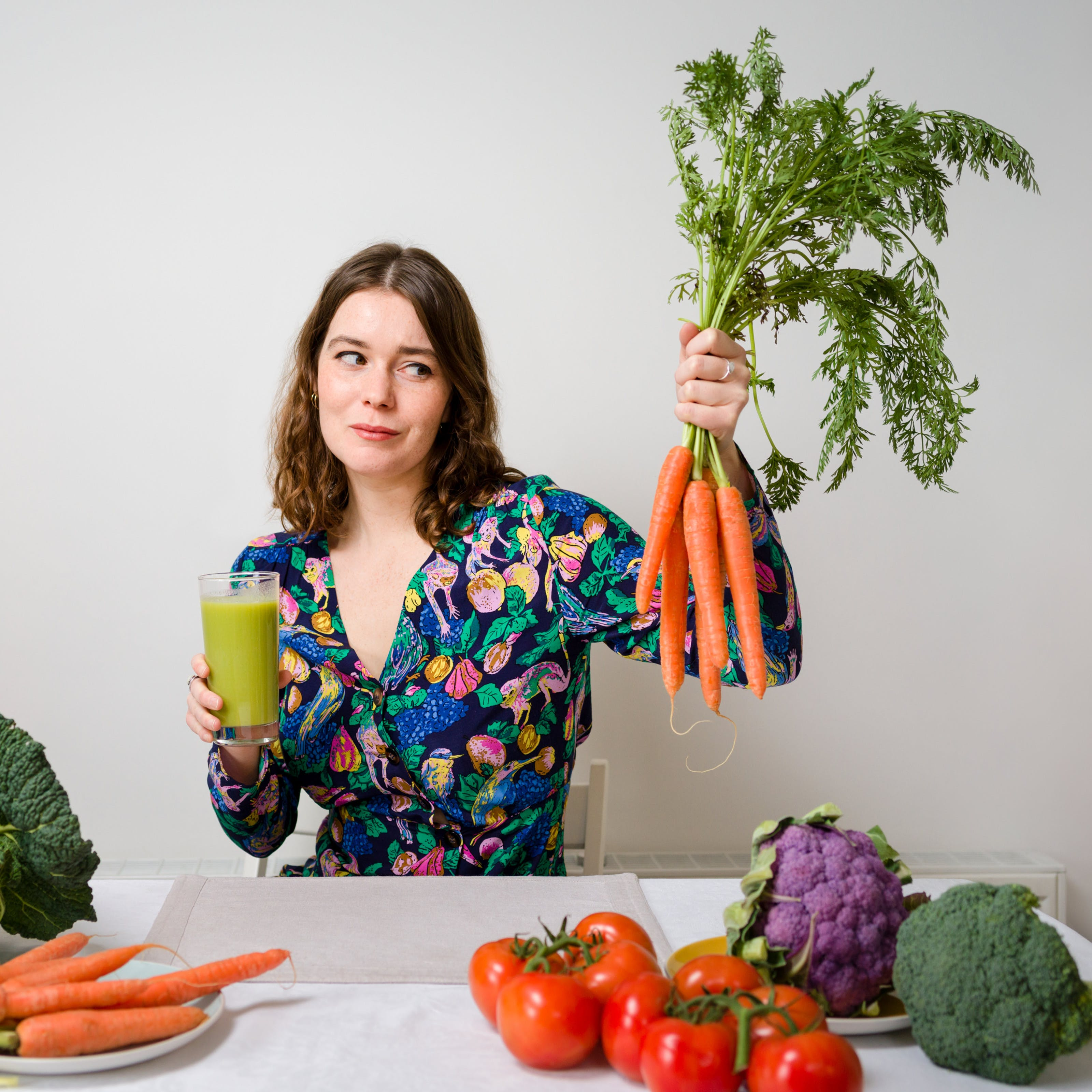 Photograph of writer Gwen Smith sat behind a table which is covered in vegetables, holding carrots in one hand and a green health drink in the other. She is looking sceptically at the vegetables.