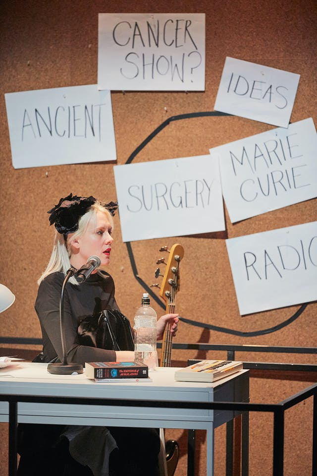 A woman with a guitar sits at a desk. There's a noticeboard behind her with words pinned up behind her: 'Cancer show?', 'Ancient', 'Ideas',  'Surgery', 'Marie Curie'.