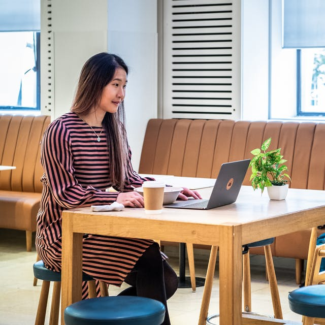 Photograph of a café interior. A woman is sat at a high table working on an open laptop. To her right is a disposable coffee cup and to her left is a small pot plant. In the background another woman is sat on a long bench seat at a table. She is also working on an open laptop