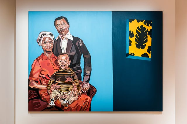 Photograph of an exhibition gallery space showing a section of light pink coloured wall on which a large colourful oil painting has been hung. The painting shows a family portrait of a seated mother with a young child on her lap and a standing father figure. The background of the painting is shades of blue with a window out to a yellow background with black leaf motifs.