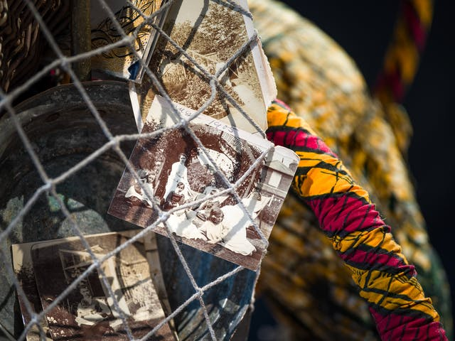 Photograph of a close-up detail of the net being carried by a life-size artwork of a figure resembling an astronaut. Within the net is a collection of black and white photographic prints showing family scenes from the early 20th century.