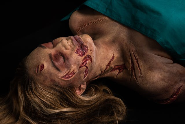 Photograph of a the head and shoulders of a woman lying on her back on a black background. Her chest is covered with a green surgical sheet. She has her eyes closed and her blond hair falls back onto the tabletop. She has prosthetic makeup applied which creates the realistic effect of her face, neck and shoulders having been slashed with a knife. The makeup reveals the layers below the skin. By her left shoulder there is makeup which creates the impression of a long surgical cut which has been stitched up.