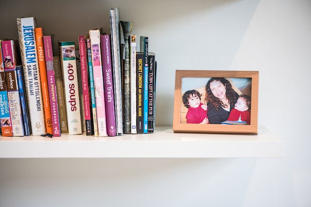 Photograph showing a shelf with a family photo in a frame of a mother and two small children. To the left of the photo is a collection of books.