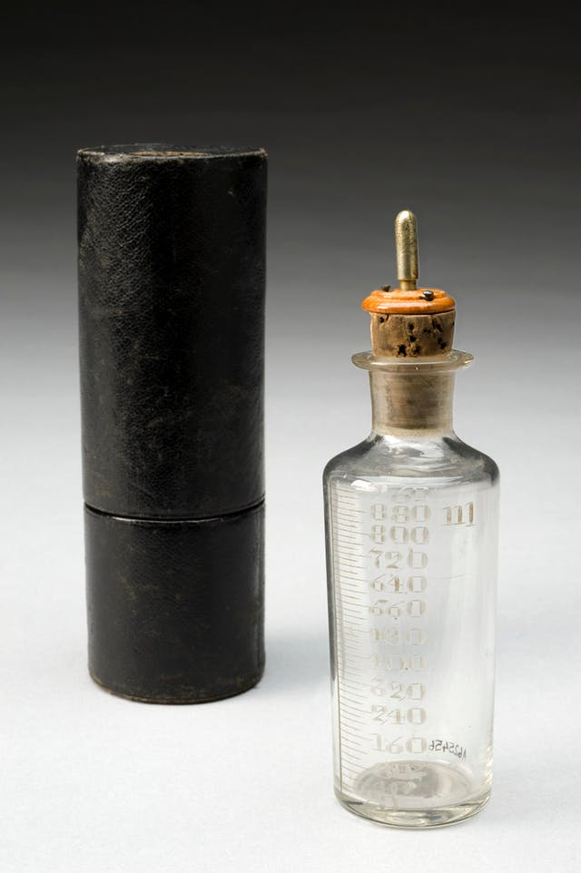 Colour photograph of a glass bottle and its case