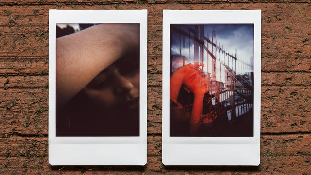 Photograph of two Instax Mini instant film prints in a line, resting on a textured brick surface. The two prints feature the same woman. The print on the left shows a close-up of her face, with her right arm raised over their forehead showing the hair on her arm. The print on the right shows the her reclining against a set of railings in an outside urban scene. Her face is lit with a red light and there is a sense of a double exposure.