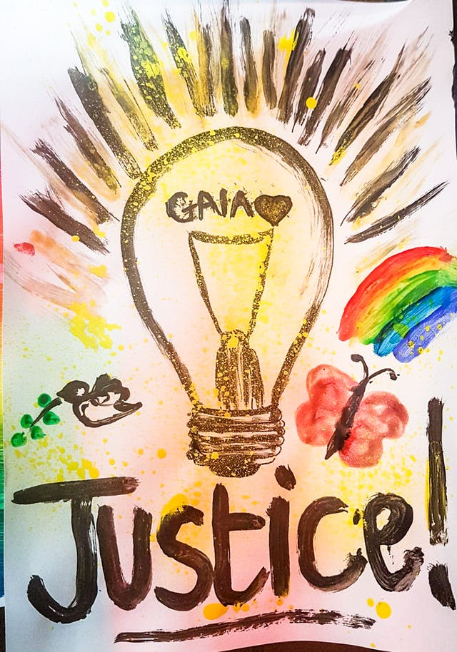 Photograph of an artwork depicting a light bulb withe the name Gaia inside, and the word 'justice' beneath. The light bulb is surrounded by a rainbow, a butterfly and a dove.