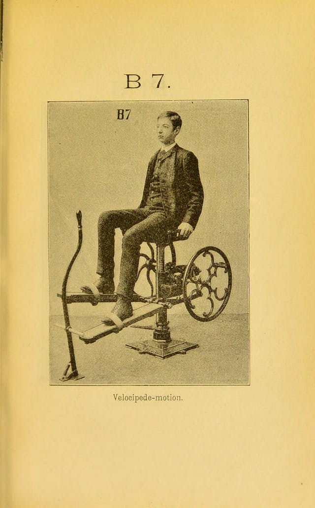 "Black and white photograph from a book with yellowing pages showing a young man seated in a contraption with two wheels to each side of him, to which are affixed planks that his feet are strapped to for the purpose of exercise. Label reads ""velocipede-motion""."