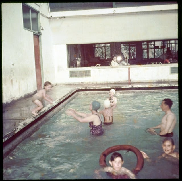 Colour photograph of families in the pool at the Peckham Pioneer Health Centre, showing a child jumping in, a woman and girls wearing rubber swimming hats, and a child with an inflatable ring. In the background is a window through which people are sitting watching the swimmers.