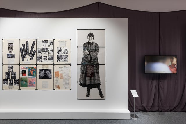 Photograph of a gallery wall showing several laminated sheets of collaged text and photographs. Behind the gallery wall is a draped fabric. to the right is a television screen showing a still from a film.