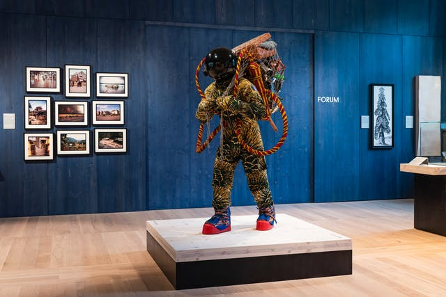 A photograph showing a life-size figure standing on a low wooden platform mounted on a black plinth beyond which is a dark blue painted wooden panelled wall on which exhibits hang. The life-size figure wears: blue and red cotton patterned moon boots with red rubber souls; a green and yellow patterned cotton space suit and gloves; and a reflective black spherical helmet. The refugee astronaut carries a net on his or her back filled with possessions such as a suitcase, a book, a teapot, and a telescope . On his or her back, there are also breathing tanks with long tubes connected to the spacesuit made from red and yellow patterned cotton.