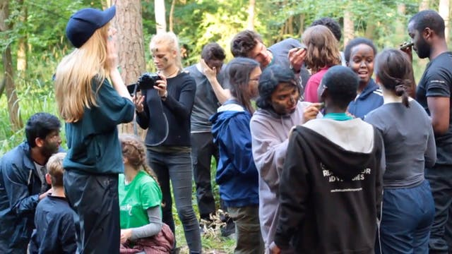 Film still showing young people painting their faces in a forest, part of
