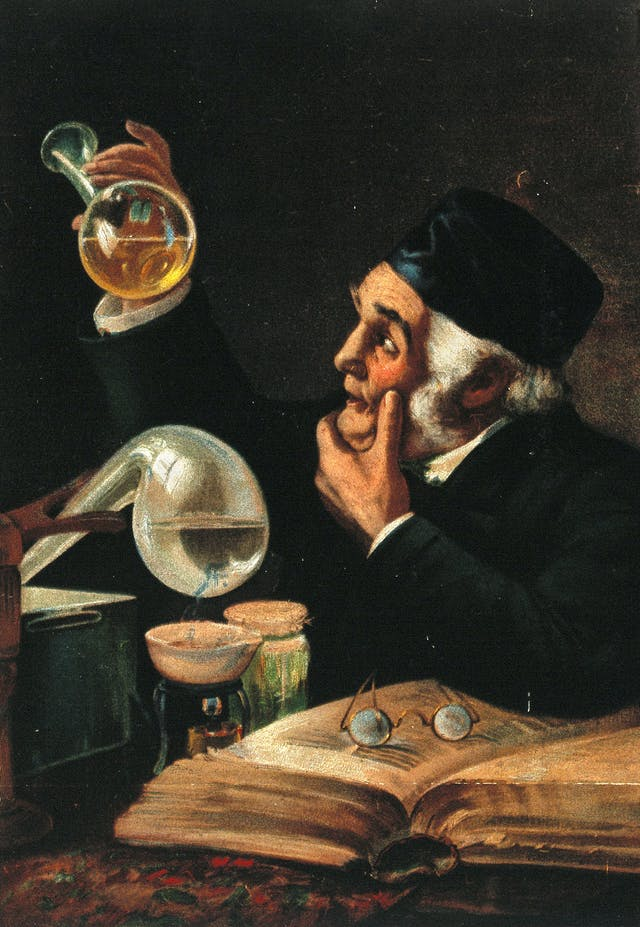 Colour print of a man seated at a desk holding a flask of yellow liquid up to the light.