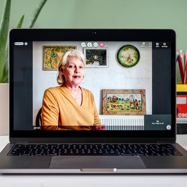 Janet Tyson appearing on a video call on a laptop, she has short shoulder-length hair and is wearing a yellow top with three pictures and a green plate hanging on a white wall behind her. On the table around the laptop is a succulent plant and a pot of colouring pencils against a green wall.