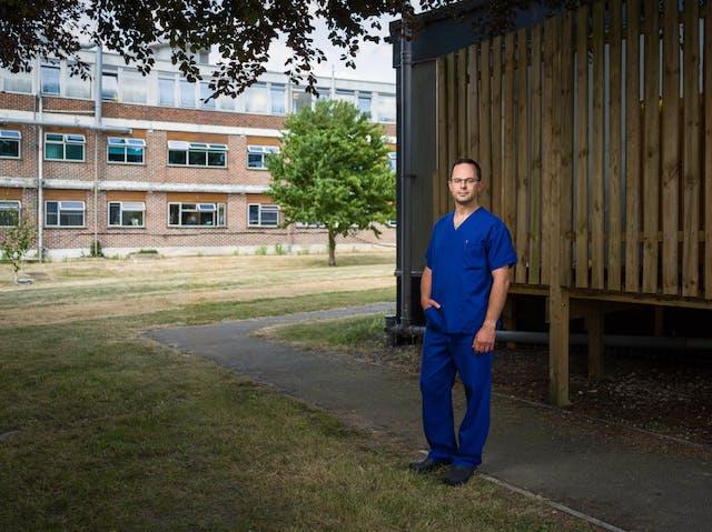 Photographic full length portrait of Ben Silverman, consultant anaesthetist, outside Harefield Hospital, Uxbridge.