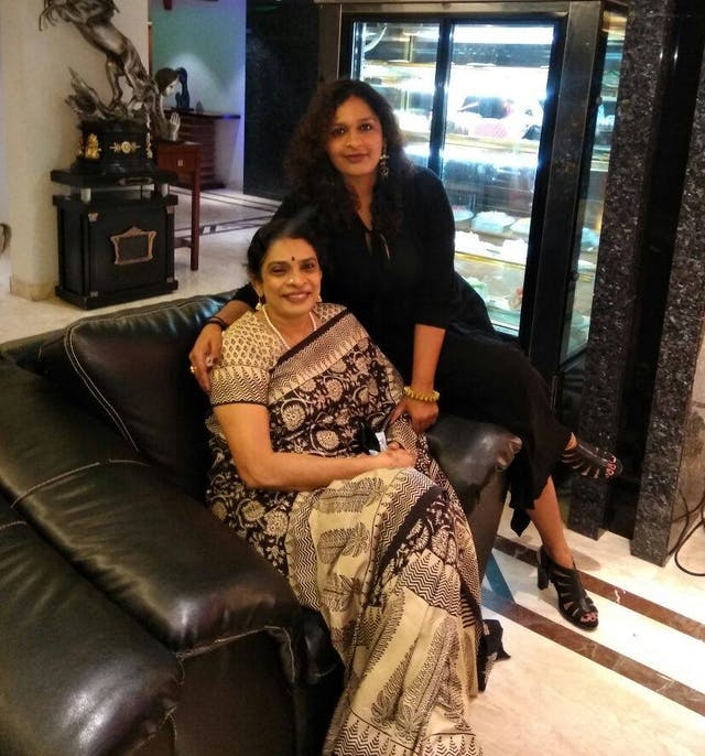 Two Indian women sat on a sofa posing for a photograph in their living room