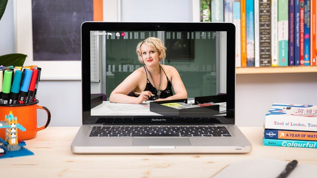 Photograph of a laptop on a desk, on the screen is a photographic portrait of Dr Kate Lister sat at a table with a selection of archive material from Wellcome Collection's sex worker card collection laid out in front of her. Around the laptop is an open notebook and pen, a pile of books and pens in a pot. In the background are bookshelves.