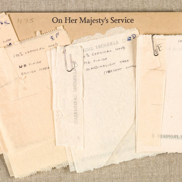 "Photograph of a selection of toilet paper samples held together with paperclips, resting on a manilla envelope printed with the words ""On Her Majesty"