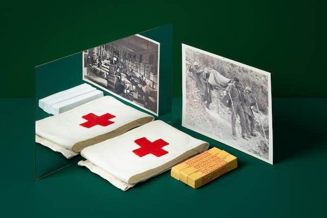 深绿色背景上的镜子照片。前景是一个带红十字的军医臂章、一包止痛药和一张二战战地军医的照片。在镜子的倒影中,是一张不同的照片,照片上是一家野战医院和空白的白色止痛药包。