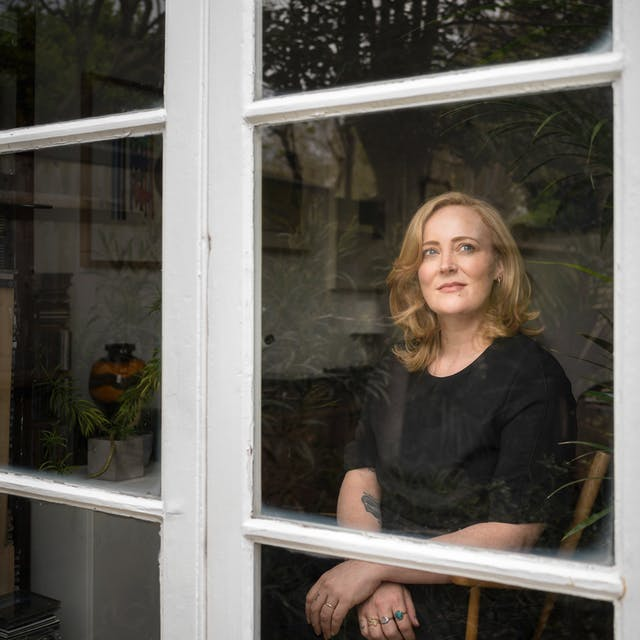 Photograph of a blonde woman with black clothing looking through a window, captured from outside.  The woman is sitting on a wooden chair with her arms crossed at the wrists with her gaze towards the top right of the frame.