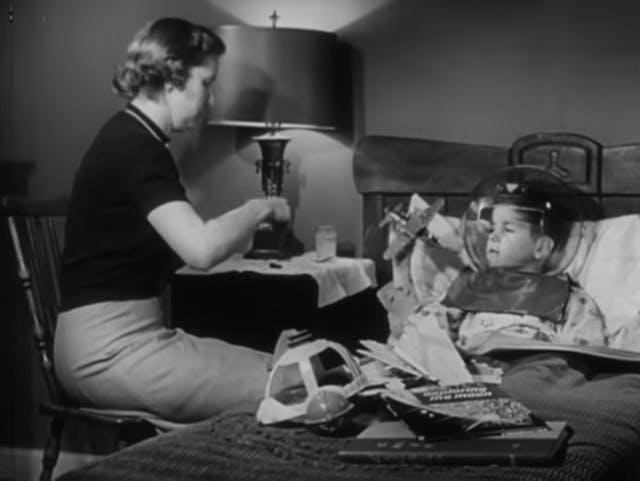 Still from black and white film featuring a boy in bed wearing an astronaut helmet costume, and a woman sat on a chair next to his bed.