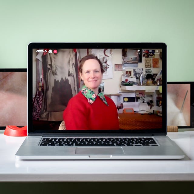 Photograph of a laptop on a desk surrounded by two more tablets. On the laptop screen is a live event showing the speaker, Amanda Couch. She has light brown hair which is tied up. She is wearing a bright red jumper with a green floral collared shirt underneath. Behind her on the wall are postcards and photographs and an artwork piece Apron Aegis (After Bartholin, Anatomia Reformata) 2019. On the tablet screens are film stills showing skin with a needle and thread. Around the screens on the desk are house plants, two cacti, notebooks, headphones and a pot of colouring pencils and paintbrushes.