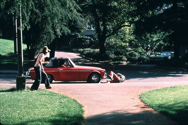 Image of a stationary red car in a road with a man lying on the pavement in front of it. Two onlookers are close by.