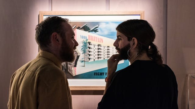 Photograph of two young men in conversation, standing in front of a poster exhibited as part of the Living with Buildings exhibition at Wellcome Collection.