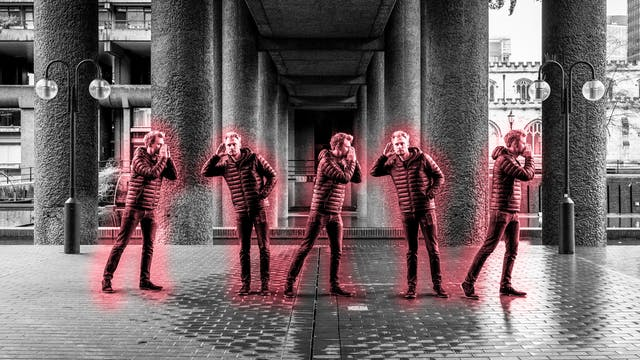 Black and white photograph of a concrete urban environment with an image of the same man repeated 5 times across the image. In each instance he is highlighted by a red glow. He appears to be passing a verbal message along to line to himself.