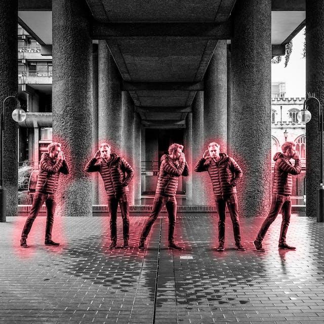 一张混凝土城市环境的黑白照片,同一个人的图像在图像中重复了5次。每一次他都被一道红光照亮。他似乎在给莱恩传递口信。