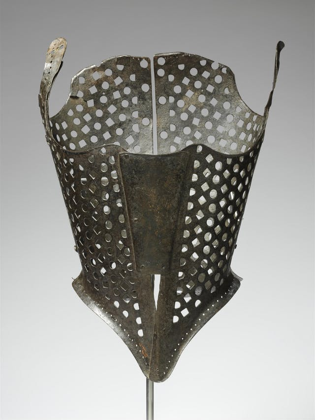 Iron bodice, corset style, made from shaped pieces of metal, square and round cutouts creating a mesh effect. Narrows at waist, tapering to a V shape in front.