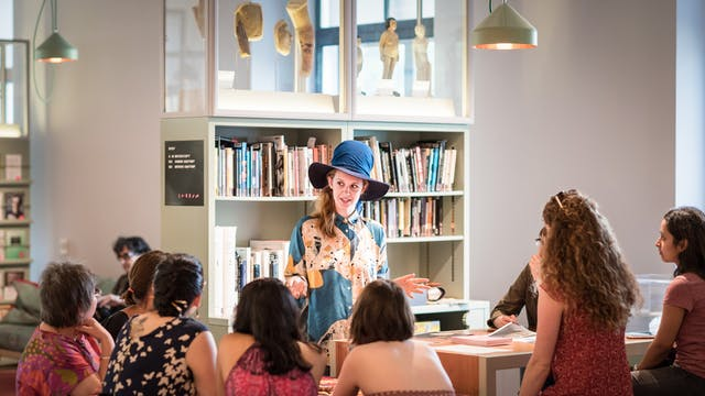 Photograph of a young woman wearing a large hat talking to a group of seated people. Behind her is the book shelves and exhibits displayed in the Reading Room at Wellcome Collection.