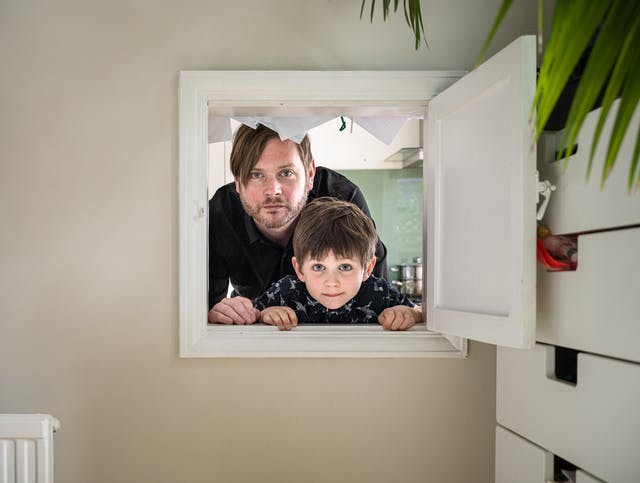 Photograph of a man and his son looking through a kitchen hatch. To the right is a chest of drawers.