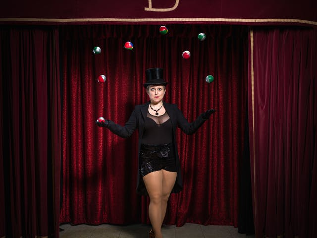 Photograph of a woman on a theatre stage surrounded by red curtains, dressed in a top hat and tails juggling 8 balls in the air.