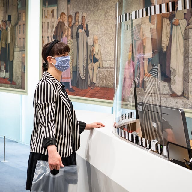 Photograph of the entrance desk of a library. Behind the desk a man stands wearing a face covering and a staff lanyard. He is talking to a female visitor standing on the other side of the desk, who is also wearing a face covering, a stripy jacket and who is holding a plastic bag. Between the two of them is a large perspex screen which runs the length of the desk. Queuing behind the visitor at the desk is a man in a pink shirt and a yellow face covering who is holding a see through plastic bag containing a laptop. On the glass partition in the background are two large figurative oil paintings.