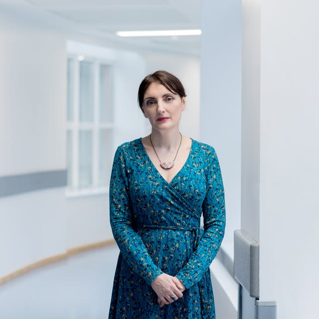 Photographic portrait of a woman wearing a blue patterned dress looking straight to camera, standing in a plain white hospital corridor.