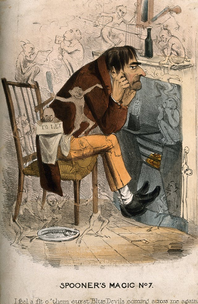 "Coloured lithograph showing a man sitting on a wooden chair in front of a stove looking glum, with his chin resting on his hands and imp-like creatures frolicking around him. Lettering reads ""I feel a fit o"