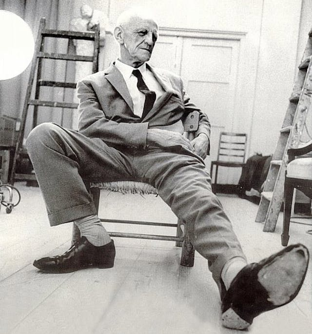 Portrait photograph of Donald Winnicott, his left foot outstretched towards the camera.