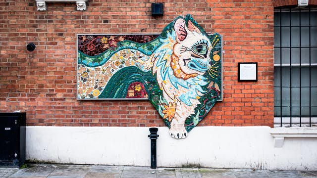 Photograph showing a brightly coloured abstract ceramic mosaic of a cat, in the style of Louis Wain. The mosaic is hung on the red brick wall of the outside of a property. Below the mosaic is the pavement and elements of street furniture. To either side are parts of window and an information plaque.