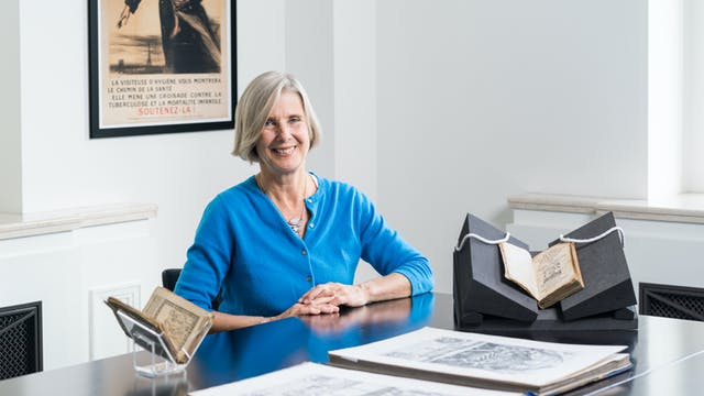 Tessa Storey with books and manuscripts in front of her on a table.