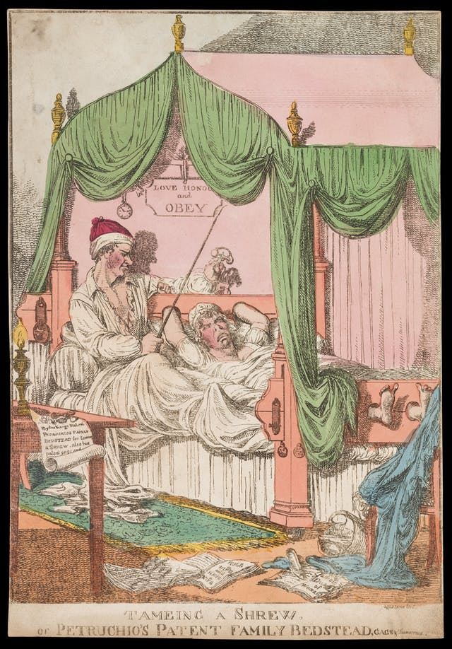 Colour illustration of a woman tied up in bed while a man sits up beside her. The husband has a whip and thumbscrews, around the floor lie sheets of paper which tell of the way a wife should behave.