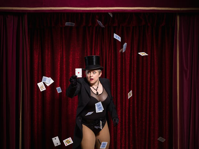 Photograph of a woman on a theatre stage surrounded by red curtains, dressed in a top hat and tails plucking the ace of hearts card out of a falling