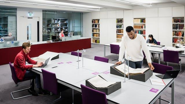 图书馆珍贵资料阅览室照片。这是一个宽镜头,显示了两张大桌子,一个咨询台和沿墙放置书籍的书架。在前台的桌子旁,一个男人正坐在一台笔记本电脑上工作。另一个人站在一个书架上,上面放着一本易碎的书。背景是另一位读者坐在远处的桌子旁。