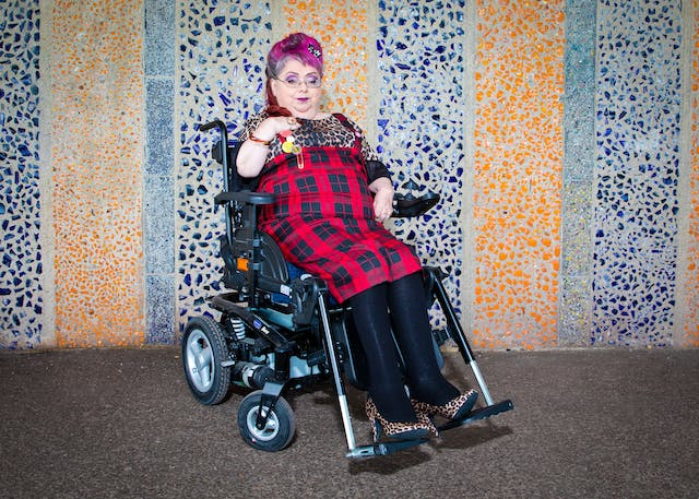 Photograph of a woman wearing a red tartan dress seated in a wheelchair, against a coloured mosaic patterned background.