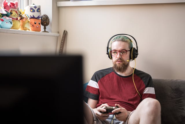 Photograph of a man wearing headphones and a microphone playing a computer game.