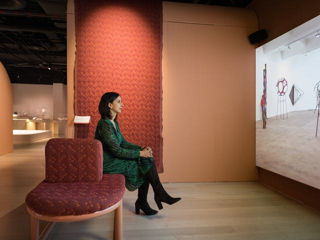 Photograph of a woman in an exhibition gallery space sitting on an upholstered bench, with her hand clasped around her crossed legs. She is watching a large projection screen to the right of frame.