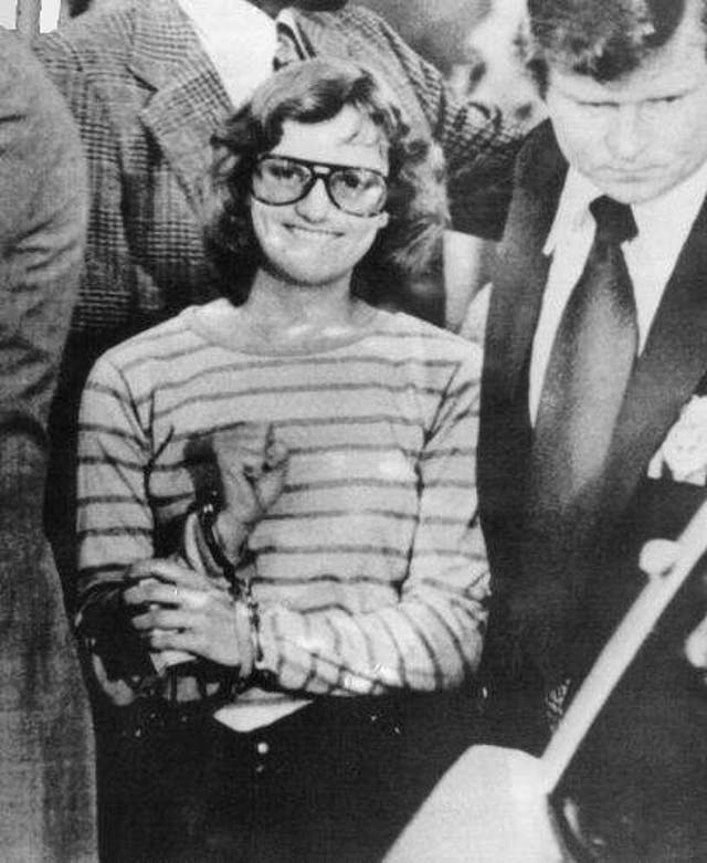 A young woman in handcuffs grins and holds a clenched fist