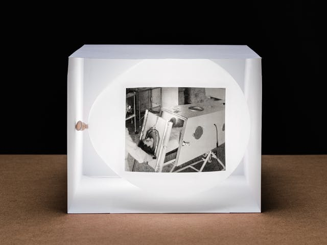 Photograph of a white inflated balloon lying horizontally within a box made of white card which is open on the side facing the camera. The balloon and box are resting on a wooden tabletop with a horizon line against a black background. The balloon looks like it is illuminated from within. On the side of the balloon is a rectangular, monochrome archive film still. The still shows a woman lying in a large metal box with her head protruding from one end. She is in the process of being slid into the box by someone's arms entering the frame from the left. The contraction is an iron lung.